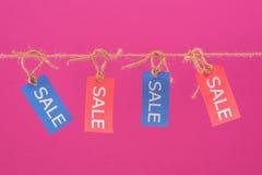 五颜六色的销售标记垂悬在桃红色隔绝的绳索 免版税库存图片