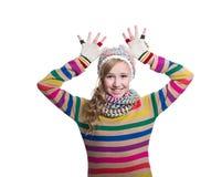 戴五颜六色的镶边毛线衣、围巾、手套和帽子的逗人喜爱的快乐的十几岁的女孩隔绝在白色背景 冬天衣裳 库存图片