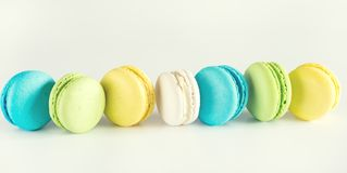 五颜六色的长期被定调子的Macarons黄色蓝绿色Macarons法国点心鲜美Macarons白色背景 免版税图库摄影