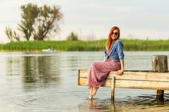 五颜六色的长的sarafan礼服的美丽的年轻红发女孩在一个木码头的一个树桩站立在河或湖 绿色bulrus 图库摄影