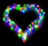 五颜六色的闪烁形成了心脏,在心脏的形状的bokeh 免版税库存图片