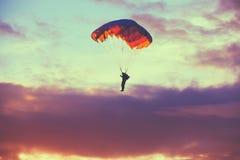 五颜六色的降伞的跳伞运动员在晴朗的天空 免版税库存照片