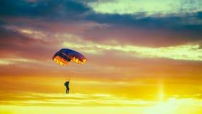 五颜六色的降伞的跳伞运动员在晴朗的日落天空 免版税库存照片
