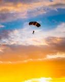 五颜六色的降伞的跳伞运动员在晴朗的日落 免版税库存照片