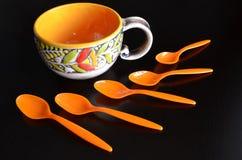 五颜六色的陶瓷杯子和橙色茶匙在黑暗的背景 免版税库存照片