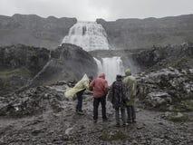 五颜六色的雨衣的旅游人观看Dynjandi w的小组  免版税库存图片
