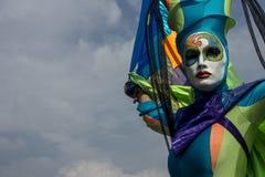 五颜六色的面具的杂技演员在天空蔚蓝 免版税图库摄影