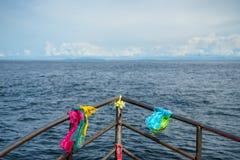 五颜六色的鞋带信念织品和丝带领带与渔夫小船头通过浩大的海海洋环绕了不锈钢路轨航行 免版税库存图片