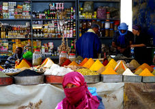 五颜六色的香料的卖主与前景妇女的有在市的souk的burqa的Rissani在摩洛哥 免版税库存照片