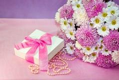 五颜六色的鲜花安排、白色当前箱子有桃红色丝带的和珍珠小珠 库存照片