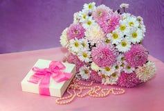 五颜六色的鲜花安排、白色当前箱子有桃红色丝带的和珍珠小珠 图库摄影