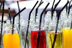 五颜六色的鸡尾酒或汁液,与秸杆的射击在小玻璃瓶 库存图片