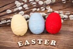 五颜六色的鸡蛋和复活节柔荑花作为欢乐装饰 库存照片