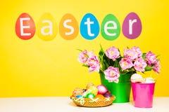 五颜六色的鸡蛋,在黄色背景的词复活节 免版税库存图片