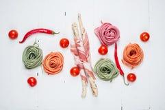 五颜六色的滚动的面团、西红柿和烟肉在白色木背景 库存照片