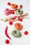五颜六色的滚动的面团、西红柿和烟肉在白色木背景 免版税图库摄影