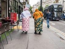 五颜六色的织品的妇女步行沿着向下伦敦街道 免版税库存图片