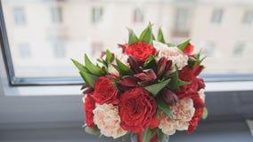 五颜六色的-红色和绿色-婚礼开花-新娘` s花束在窗口 免版税库存图片
