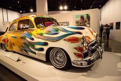五颜六色的1950年薛佛列轿车驾驶低底盘汽车兜风者叫了我们的家用汽车  免版税库存图片