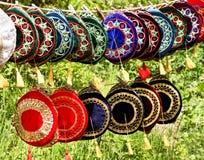 五颜六色的头骨盖帽在绿草背景 crimea's的鞑靼人传统回教游人的帽子和纪念品 免版税库存照片