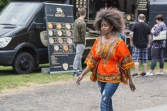 五颜六色衣裳微笑的年轻美丽的非洲妇女未经预约而来 免版税库存照片