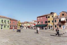 五颜六色被绘的房子和正方形与人在Burano海岛,意大利上 免版税库存照片