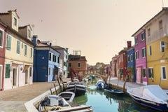 五颜六色被绘的房子和运河有小船的在Burano海岛,意大利上 免版税库存照片