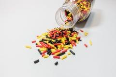 五颜六色洒从在白色桌上的一个瓶子溢出 免版税图库摄影