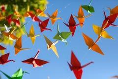 五颜六色origami鸟飞行 1个背景覆盖多云天空 免版税库存图片