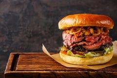 五香熏牛肉汉堡用切的烤牛肉和葱油煎圆环 免版税图库摄影