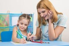 五年女孩和年轻母亲一起绘与蜡笔的一幅画 库存图片