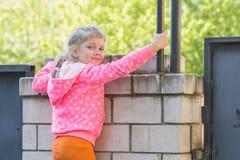 五年女孩在砖篱芭上升了并且转动了看框架 免版税库存照片
