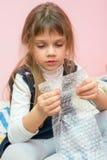 五年女孩坐床和吃包装包裹的泡影 库存照片