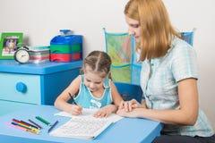 五年女孩学会恰当地写信,家庭教师帮助她 图库摄影