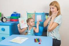 五年女孩绘了一个母亲并且显示愉快她的母亲惊奇和 免版税图库摄影