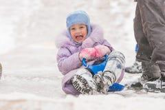 五年女孩滚动在冰幻灯片下几乎碰撞了入其他孩子 图库摄影