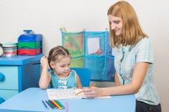 五年女孩画铅笔在笔记本和调查框架 库存图片