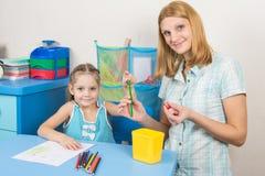 五年孩子在铅笔母亲的技巧在框架投入了手指和一起看了 图库摄影