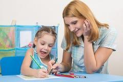 五年获得女孩和年轻的母亲画与蜡笔的乐趣愉快的图画 库存图片