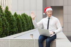 井喂!在圣诞老人帽子的幸福商人,看照相机和送你好标志 免版税图库摄影