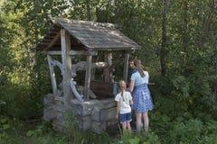 以井的形式,孩子获取从春天的泉水 免版税图库摄影