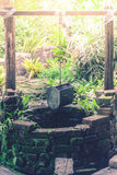 水井老砖与垂悬在木材的桶在庭院里 免版税库存图片