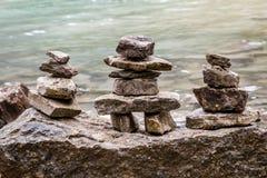 亚伯大,加拿大- Inukshuk由湖的岩石堆 免版税库存照片