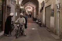 亚兹德,伊朗- 2016年8月18日:穿传统衣裳的伊朗阿訇谈论,当在摩托车在Yaz时一条被盖的街道  免版税库存照片