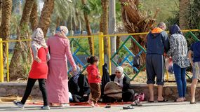 亚喀巴,约旦, 2018年3月7日:回教家庭采取休息在海滩的后面亚喀巴 免版税库存图片