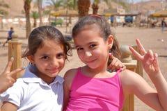 亚喀巴,约旦- 2016年3月15日:微笑在海滩的两个逗人喜爱的小女孩画象  库存照片