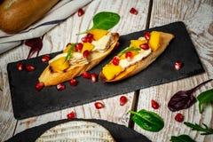 亚尔方索芒果敬酒乳酪 Bruschetta用芒果和乳酪 自创 健康素食nutritionon木背景, 免版税图库摄影