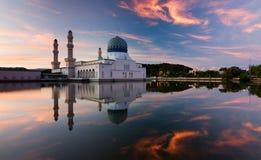 亚庇日出的市清真寺的反射在沙巴,东马来西亚 库存图片