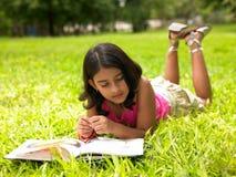 亚洲书女孩公园读取 免版税库存图片