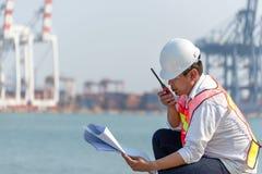 亚洲人工程师收音机和方案和与容器货物货物船一起使用在造船厂黄昏的后勤进口商展的 免版税图库摄影